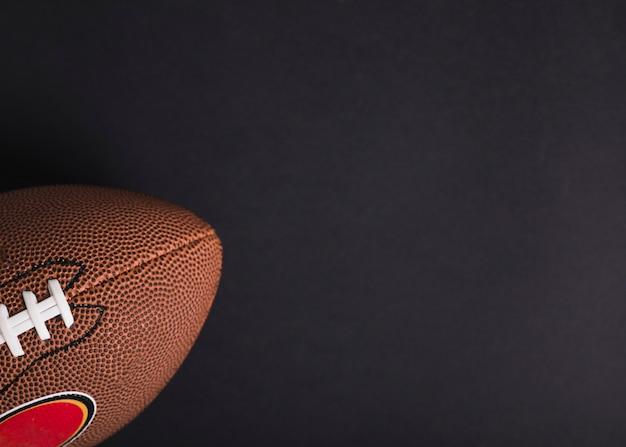 Primo piano della palla di rugby marrone su sfondo nero