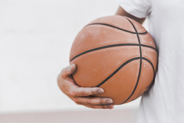 Primo piano della pallacanestro della tenuta della mano di un giocatore maschio