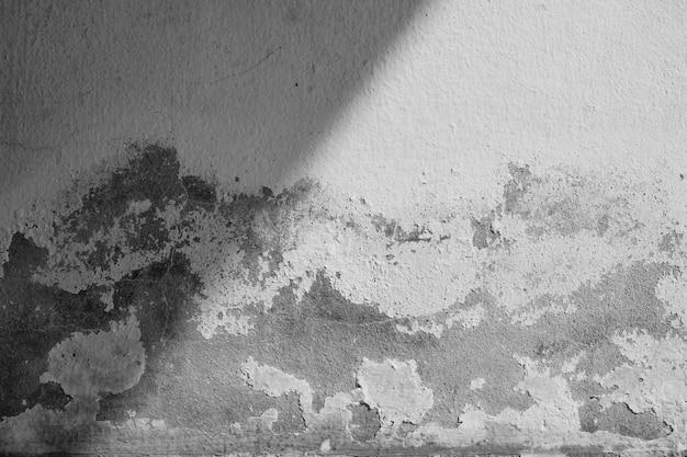 Primo piano della parete della crepa del cemento bianco e della vernice sbucciata causate da acqua e da luce solare. sbucciare la parete di vernice bianca con macchia nera. bianco e nero di sfondo texture.