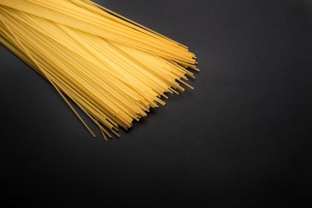 Primo piano della pasta lunga gialla degli spaghetti sul piano di lavoro della cucina