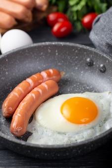 Primo piano della pentola con l'uovo e le salsiccie per la prima colazione