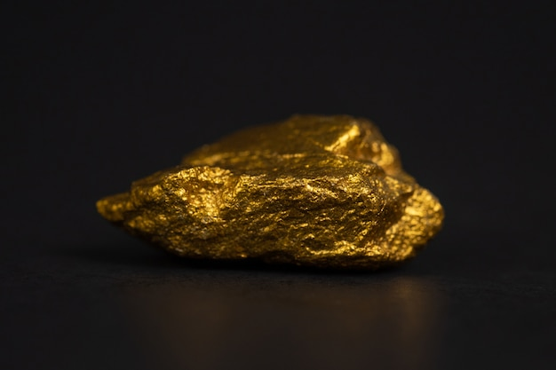 Primo piano della pepita di oro o minerale di oro sul nero