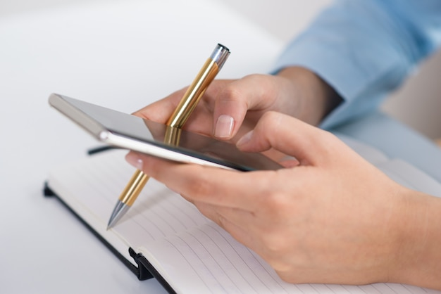 Primo piano della persona che manda un sms sullo smartphone e che lavora allo scrittorio
