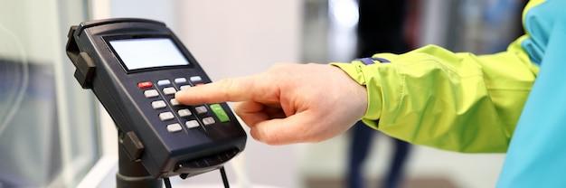 Primo piano della persona che preme i bottoni sulla macchina della carta. equipaggia il dito inserendo il codice pin nell'organizzazione. attrezzature per pagare più velocemente. tecnologia moderna e concetto di pagamento rapido