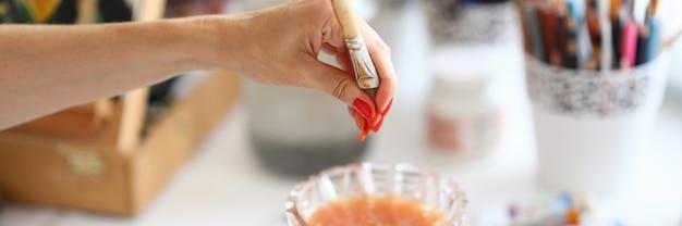 Primo piano della persona lavare in acqua e strizzare il pennello.