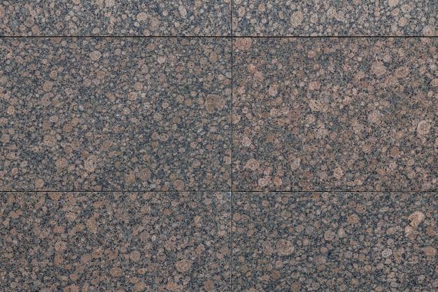Primo piano della piastrella marrone rossiccio chiazzata e del granito nero