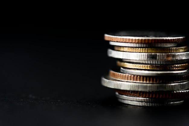 Primo piano della pila delle monete isolata su fondo nero