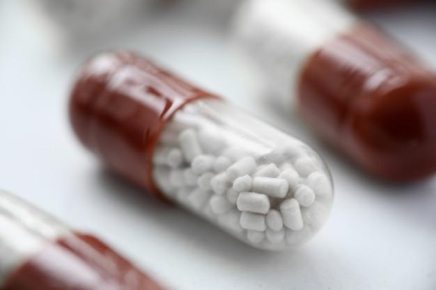 Primo piano della pillola rossa e bianca sul tavolo. medicinali per un recupero più rapido. prenditi cura di un adulto malato. compressa da deglutire. medicina moderna e cure mediche per il concetto di paziente