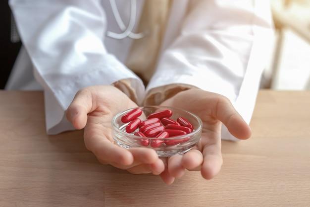 Primo piano della pillola rossa nella mano della donna.