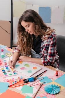 Primo piano della pittura dell'artista femminile alla pagina bianca