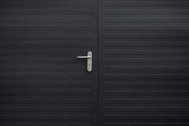 Primo piano della porta di metallo nero con maniglia grigia