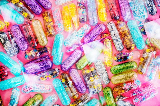 Primo piano della priorità bassa lucida luccicante della capsula delle pillole di luccichio