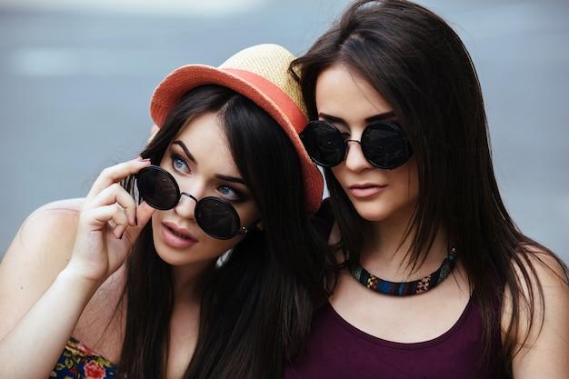 Primo piano della ragazza che gioca con i suoi occhiali da sole accanto alla sua amica