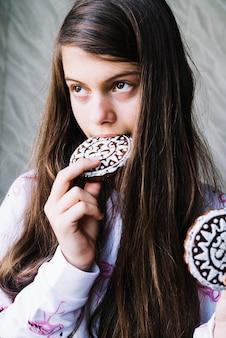 Primo piano della ragazza che mangia i biscotti cotti