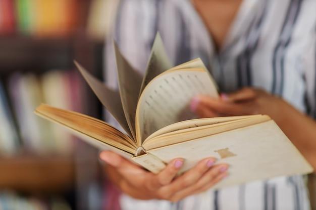 Primo piano della ragazza che passa in rassegna il libro mentre levandosi in piedi in biblioteca