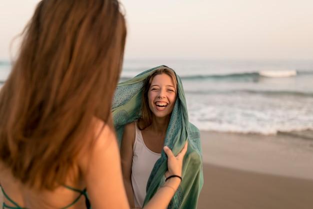 Primo piano della ragazza che si diverte con la sua amica sulla spiaggia