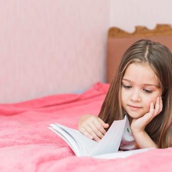 Primo piano della ragazza che si trova sul libro di lettura del letto
