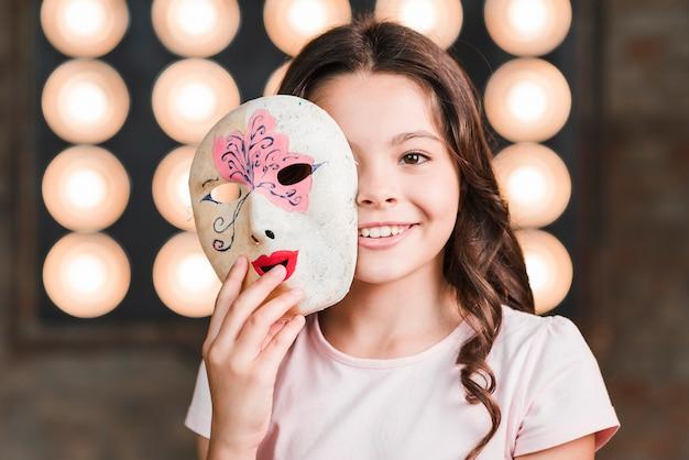 Primo piano della ragazza che tiene la mascherina veneziana davanti al suo fronte