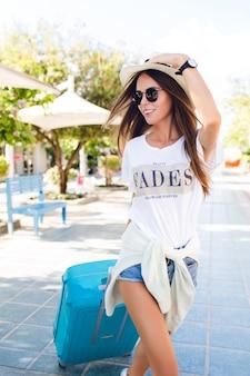 Primo piano della ragazza giovane abbronzata sottile che cammina in un parco con la valigia blu dietro di lei. indossa pantaloncini di jeans, maglietta bianca, cappello di paglia e occhiali da sole scuri. sorride e tiene il cappello con una mano