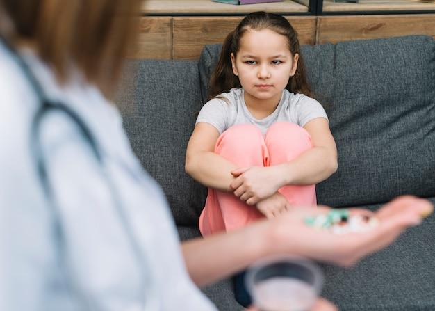 Primo piano della ragazza seria che si siede sul sofà che esamina medico che dà medicina