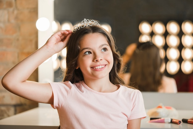 Primo piano della ragazza sorridente che indossa corona che daydreaming