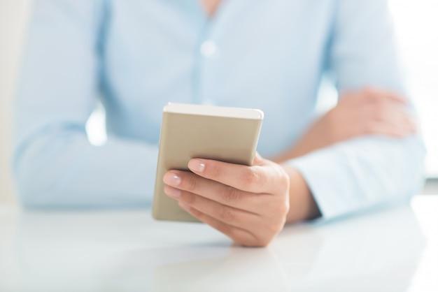 Primo piano della rete della persona sullo smartphone alla tavola