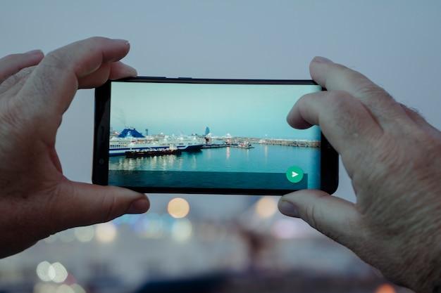 Primo piano della retrovisione di alcune mani che prendono le foto con il cellulare in un porto marittimo al crepuscolo