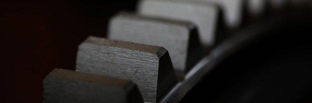 Primo piano della ruota dentata del metallo su fondo scuro come parte della macchina piena