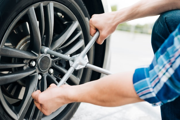 Primo piano della ruota di automobile cambiante dell'uomo