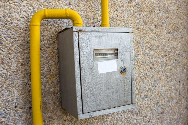 Primo piano della scatola del contatore del gas d'acciaio del metallo con i tubi gialli di collegamento che appendono sulla parete esterna della casa della pietra leggera.