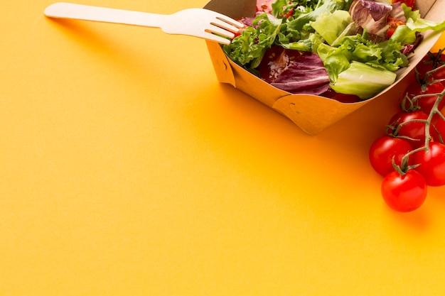 Primo piano della scatola di insalata deliziosa con i pomodori