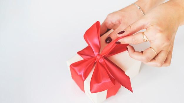Primo piano della scatola regalo di scartare della mano della donna su fondo bianco