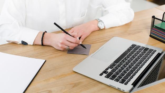 Primo piano della scrittura della donna di affari sulla nota adesiva con la penna sopra lo scrittorio di legno