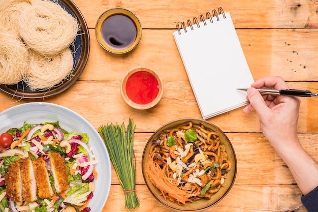 Primo piano della scrittura di una persona sul blocco note con penna vicino al cibo tailandese sulla tavola di legno