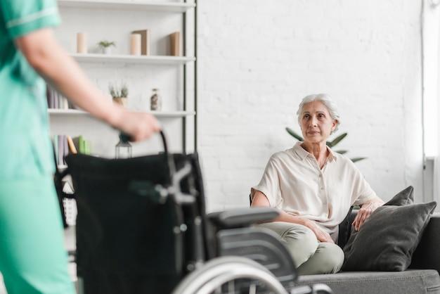 Primo piano della sedia a rotelle della tenuta dell'infermiere davanti al paziente femminile senior