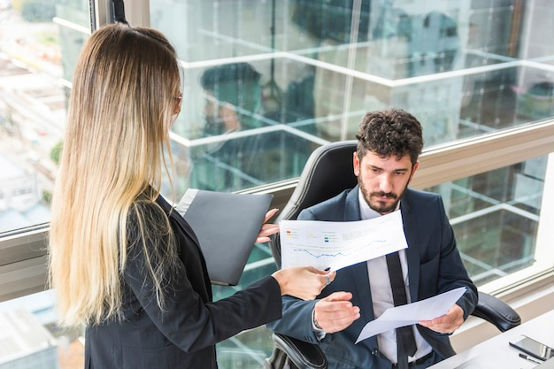 Primo piano della segretaria femminile che dà rapporto finanziario al responsabile maschio sul posto di lavoro
