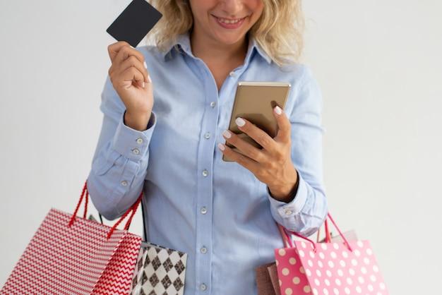 Primo piano della signora sorridente che legge gli sms mentre andando a fare spese