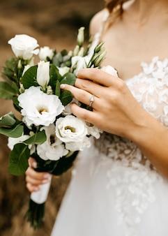Primo piano della sposa che indossa l'anello di diamanti, che tiene un bouquet da sposa