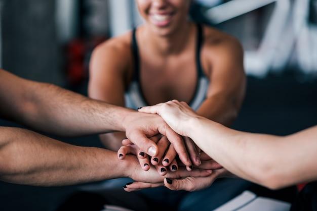 Primo piano della squadra di sport che impila le mani mentre sedendosi nella palestra.