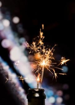 Primo piano della stella filante bruciante in bottiglia sul fondo del bokeh