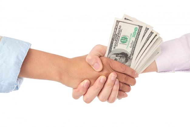 Primo piano della stretta di mano con le banconote in dollari nel mezzo