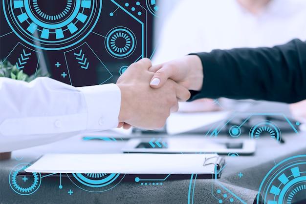 Primo piano della stretta di mano degli esseri umani con il fondo di tecnologia