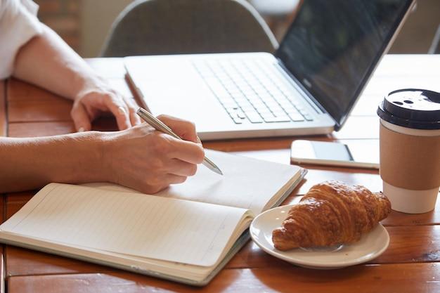Primo piano della tavola di prima colazione con le mani femminili che posano informazioni al pianificatore quotidiano