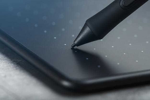 Primo piano della tavoletta grafica e della penna su un fondo strutturale grigio. gadget per lavorare come designer, artista e fotografo.
