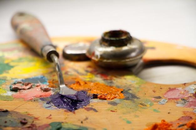 Primo piano della tavolozza con vernici colorate e spatola sulla superficie bianca