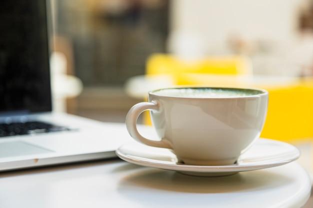 Primo piano della tazza bianca con il latte del tè verde vicino al computer portatile sulla tavola bianca