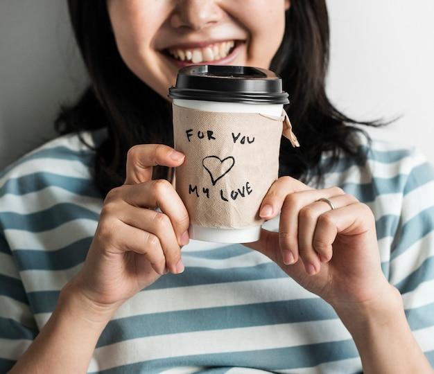 Primo piano della tazza di caffè asiatica della tenuta della donna