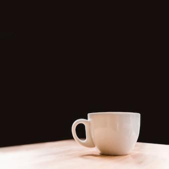 Primo piano della tazza di caffè bianco sullo scrittorio sopra il contesto nero