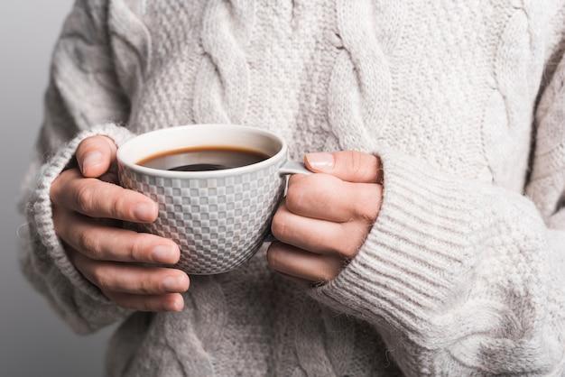 Primo piano della tazza di caffè della holding della mano della donna