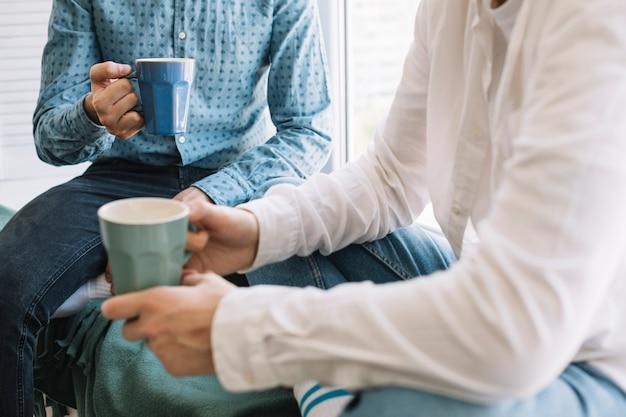Primo piano della tazza di caffè della holding della mano di due amici